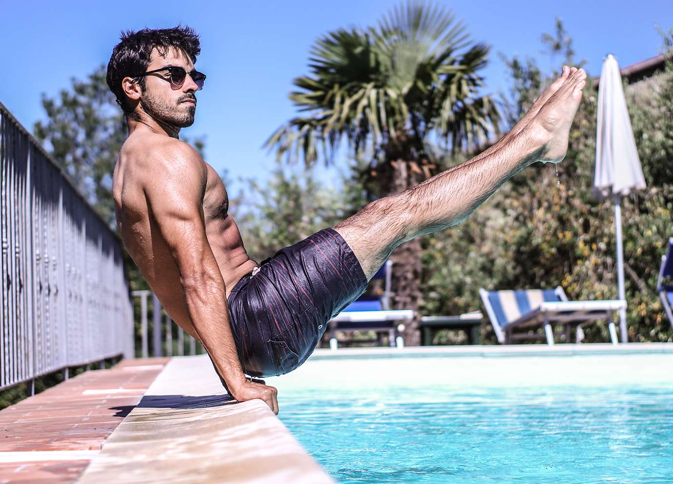 Homme faisant de la callisthénie au bord de sa piscine